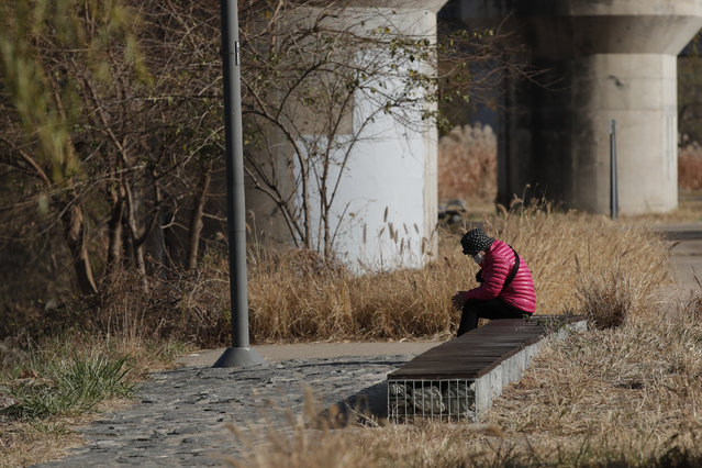 A woman wearing a face mask as a precaution against the coronavirus, sits on a bench while maintaining social distancing at a park in Seoul, South Korea, Thursday, November 26, 2020. (Photo by Lee Jin-man/AP Photo)