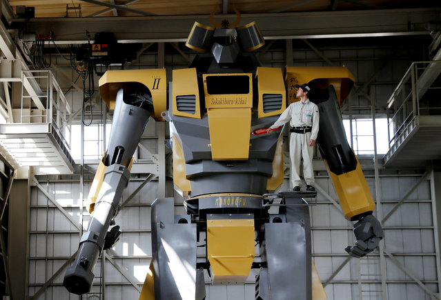 Sakakibara Kikai's engineer Go Sakakibara poses with the bipedal robot Mononofu during its demonstration at its factory in Shinto Village, Gunma Prefecture, Japan on April 12, 2018. Developed at Sakakibara Kikai, a maker of farming machinery, LW-Mononofu is a 28-feet tall, two-legged robot weighing in at more than 7 tonnes. It contains a cockpit with monitors and levers for the pilot to control the robot's arms and legs. (Photo by Kim Kyung-Hoon/Reuters)
