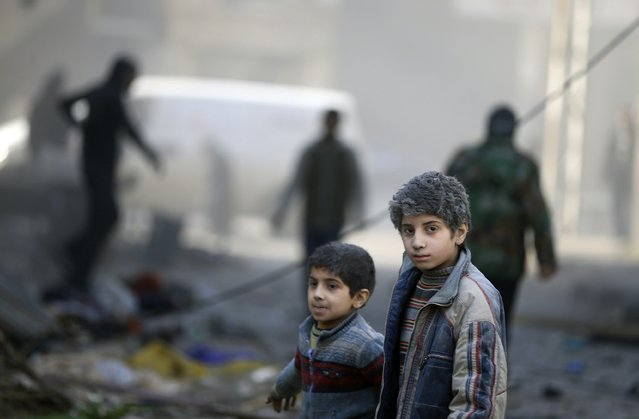 Children covered with dust walk at a site hit by what activists said was an air strike by forces of Syria's President Bashar al-Assad in the Duma neighbourhood of Damascus December 27, 2014. (Photo by Bassam Khabieh/Reuters)