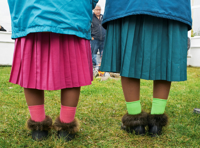 Madeline Champlain and Marie Flunkie, two elders visiting from the community of Whati, wear traditional moccasins with bright socks and skirts at a spiritual gathering in Deline, Northwest Territories, Canada September 7, 2016. (Photo by Pat Kane/Reuters)