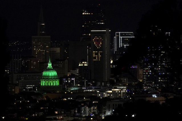 City Hall in San Francisco is illuminated in green to mark the fifth anniversary of the Paris climate accord, Saturday, December 12, 2020. (Photo by Jeff Chiu/AP Photo)