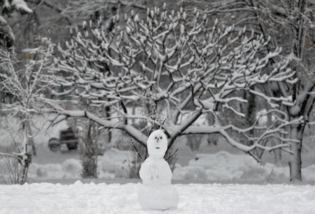 A snowman made by children is backdropped by trees covered in snow in  a park in Bucharest, Romania, Monday, December 29, 2014. Romania, especially the eastern part,  is affected by heavy snow falls and blizzards this year  that cause traffic disruptions but are enjoyed by children and mountain tourists. (Photo by Vadim Ghirda/AP Photo)