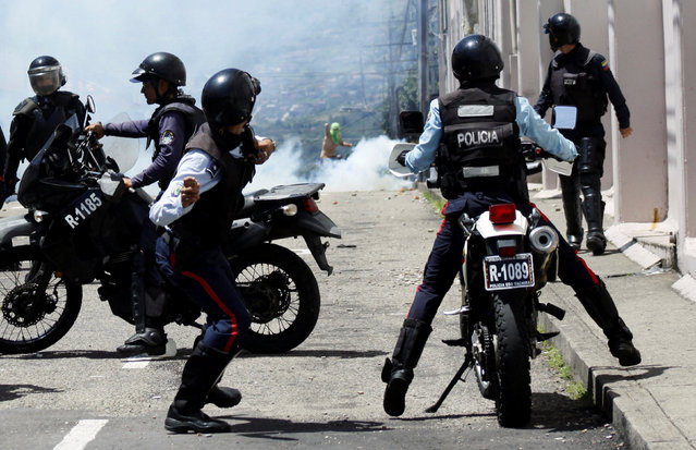 A riot police officer throws a stone during clashes with opposition supporters in a rally to demand a referendum to remove President Nicolas Maduro in San Cristobal, Venezuela October 24, 2016. (Photo by Carlos Eduardo Ramirez/Reuters)