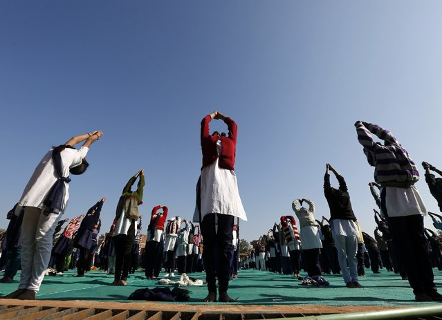 Schoolchildren offer prayers to Sun god during a yoga session at a camp in the western Indian city of Ahmedabad January 6, 2015. (Photo by Amit Dave/Reuters)