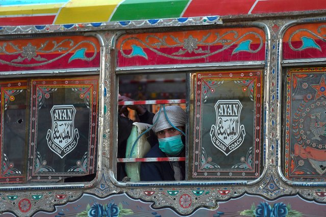 A man wearing a facemask as a preventive measure against the Covid-19 coronavirus, travels on a passenger bus in Karachi on December 17, 2020. (Photo by Asif Hassan/AFP Photo)