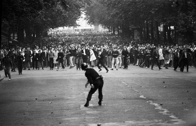 "A policeman confronts defiant students ron the Boulevard Saint-Michel during the first day of violent clashes, Cluny Boulevard Saint-Michel, at the intersection of Boulevard Saint-Germain, Paris France, May 6, 1968 . In all, 1,045 civilians were wounded during what became known as ""the night of the barricades"". (Photo by Gökşin Sipahioğlu/SIPA Press)"