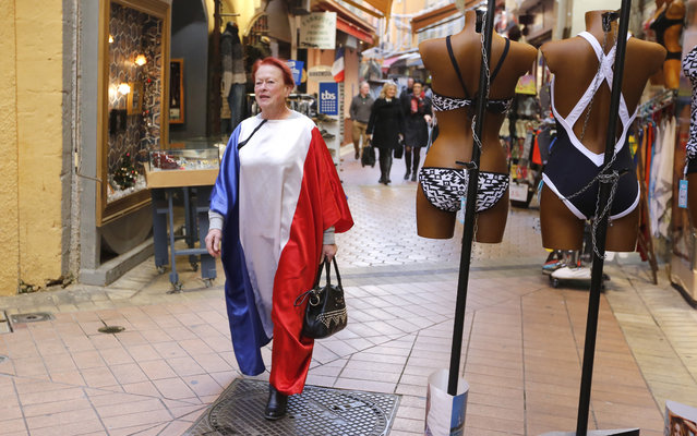 Eliane Ciesco, citizen of Nice, wearing a dress in the colors of the French flag, walks in a street of Nice, southeastern France, Friday, November 27, 2015. French President Francois Hollande called on his compatriots to hang French tricolor flags on Friday to pay homage to the victims of the Nov. 13 attacks, an unusual appeal by a Socialist leader in a country where flag-waving is often associated with nationalists and the far right. (Photo by Lionel Cironneau/AP Photo)