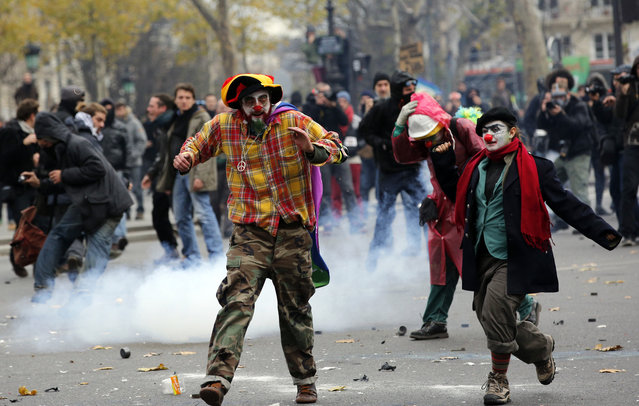 Activists run as they clash with policemen during a protest ahead of the 2015 Paris Climate Conference, in Paris, Sunday, November 29, 2015. (Photo by Christophe Ena/AP Photo)