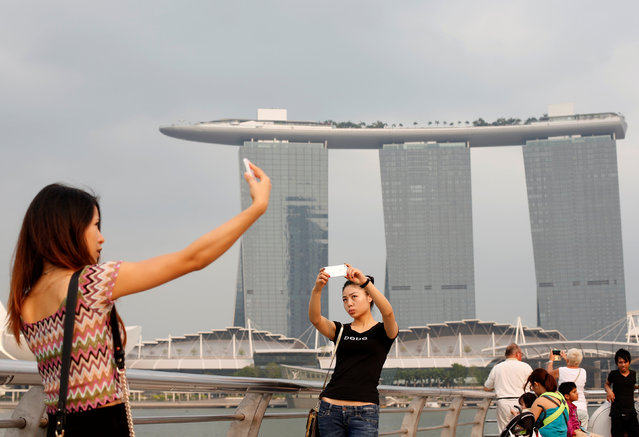 People take photos of themselves at a tourist landmark overlooking the Marina Bay Sands casino in Singapore March 4, 2014. (Photo by Edgar Su/Reuters)