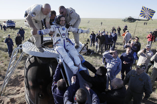 Russian space agency rescue team help Russian cosmonaut Anton Shkaplerov U.S. out from the capsule shortly after the landing of the Russian Soyuz MS-07 space capsule about 150 km (80 miles) south-east of the Kazakh town of Zhezkazgan, Kazakhstan, Sunday, June 3, 2018. A Soyuz space capsule with Russian cosmonaut Anton Shkaplerov, U.S. astronaut Scott Tingle and Japanese astronaut Norishige Kanai, returning from a mission to the International Space Station landed safely on Sunday on the steppes of Kazakhstan. (Photo by Dmitry Lovetsky/AP Photo)