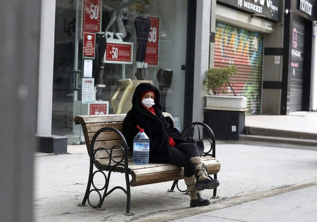 A woman wearing a mask to help protect against the spread of coronavirus, rests in a deserted street after shopping for food during a two-day weekend curfew, in Ankara, Turkey, Sunday, January 24, 2021. Turkey has passed the milestone 25,000 COVID-19 deaths on Sunday. (Photo by Burhan Ozbilici/AP Photo)