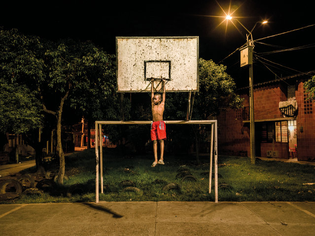 Didiller Angulo, nine, on the basketball court in Potrero Grande. People only moved to Potrero Grande about 10 years but the neighbourhood is considered one of the most troubled in the country. Extreme poverty, unemployment and lack of opportunities have propelled the area into a downward spiral of widespread drug abuse, deadly violence and deeply rooted social problems. (Photo by Mads Nissen/Politiken/The Guardian/Panos Pictures)