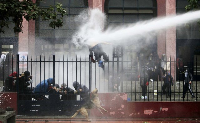 A student is hit by a jet of water sprayed by riot police during a protest against the government to demand changes in the public state education system, in Santiago June 26, 2013. Chilean students have been protesting against what they say is profiteering in the state education system. (Photo by Carlos Vera/Reuters)