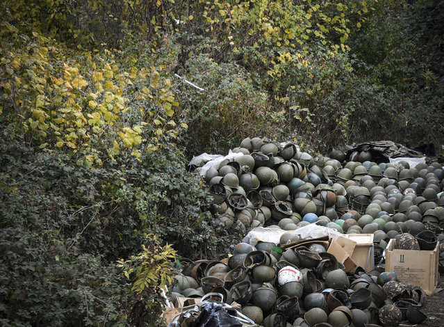A pile of Armenian army helmets lie on the ground close to an Armenian Army barracks, where soldiers say there is no indoors storage space left, on November 15, 2020, outside of the zone of the the region's administrative centre of  Stepanakert, where a Russian peacekeeping contingent deployed this week. Azerbaijan said on November 15, 2020, it had agreed to extend a deadline for Armenia to withdraw from a disputed district as part of a peace accord that ended six weeks of fierce fighting over the Nagorno-Karabakh region. Armenia lost around 2300 dead during the military conflict over this breakaway region. (Photo by Alexander Nemenov/AFP Photo)
