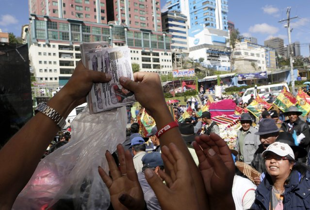 "People reach for imitation bank notes that were blessed by a witch doctor during the ""Alasitas"" fair in La Paz January 24, 2015. (Photo by David Mercado/Reuters)"