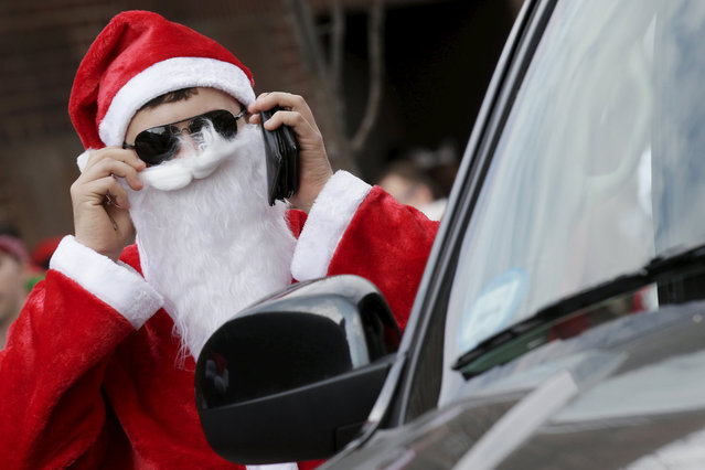 A man dressed as Santa Claus looks at himself in a car mirror during the annual SantaCon event in the Brooklyn borough of New York, December 12, 2015. (Photo by Brendan McDermid/Reuters)
