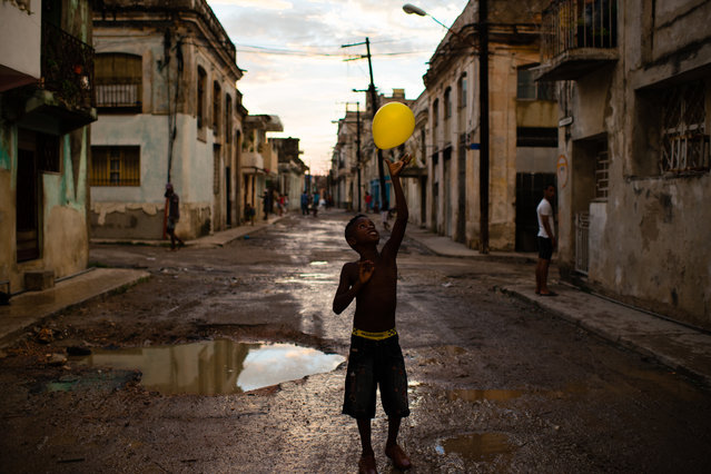 Andris Trujillo, 8, tosses a yellow balloon into the air on the evening of August 15, 2015 in the Cerro (hill) neighborhood of Havana, Cuba on August 15, 2015. (Photo by Sarah L. Voisin/The Washington Post)