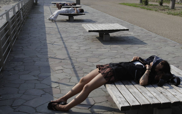 People sunbathe on benches at a park in Tokyo, Wednesday, July 10, 2013. Temperatures soared in the metropolitan area to 37.4 degrees Celsius (99.3 degrees Fahrenheit) Wednesday. (Photo by Shizuo Kambayashi/AP Photo)