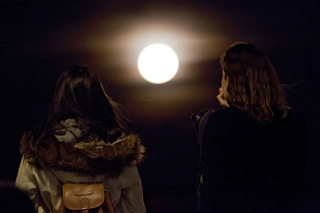 Two women watch the full moon rise above Lisbon Monday, November 14 2016. The brightest moon in almost 69 years, a phenomenon known as the supermoon, is lighting up the sky in a treat for star watchers around the globe. (Photo by Armando Franca/AP Photo)