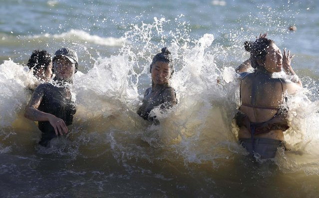 After playing in the mud, participants swim to clean themselves during the Boryeong Mud Festival at Daecheon beach in Boryeong, South Korea, on July 19, 2013. (Photo by Lee Jae-Won/Reuters)
