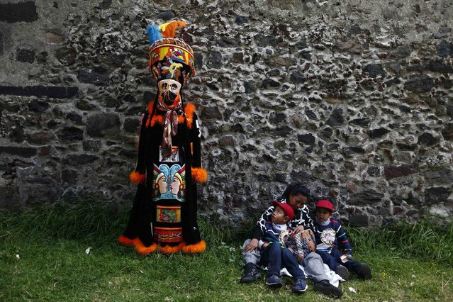A boy sitting with his family looks up at a traditional Chinelo costumed dancer during a celebration 40 days after the birth of Jesus, in Xochimilco on the outskirts of Mexico City, February 2, 2015. (Photo by Edgard Garrido/Reuters)