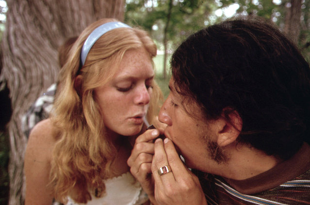 A young man and woman smoke pot during an outing near Leakey, Texas, May 1973. (Photo by Marc St. Gil/NARA via The Atlantic)
