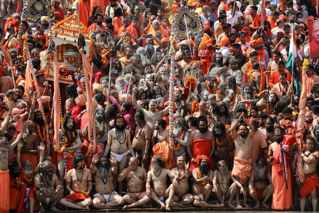"""Naga Sadhus, or Hindu holy men, get ready to take a dip in the Ganges river during the first Shahi Snan at """"Kumbh Mela"""", or the Pitcher Festival, in Haridwar, India, March 11, 2021. (Photo by Anushree Fadnavis/Reuters)"""