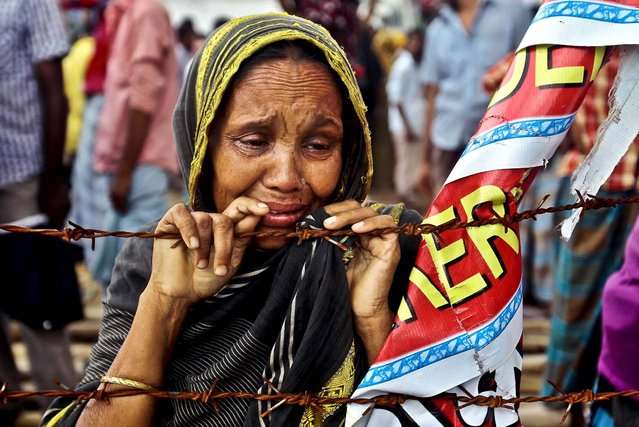 A woman cries during an event on the 100th day of the of Rana Plaza building collapse, the worst tragedy in the history of the global garment industry, near Dhaka, Bangladesh, on August 2, 2013. The collapse killed 1,129 people with many still missing. (Photo by A. M. Ahad/Associated Press)