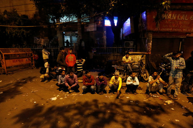 People sit in a queue as they wait for the bank to open to exchange their old high-denomination banknotes in the early hours, in the old quarters of Delhi, India, November 16, 2016. (Photo by Adnan Abidi/Reuters)