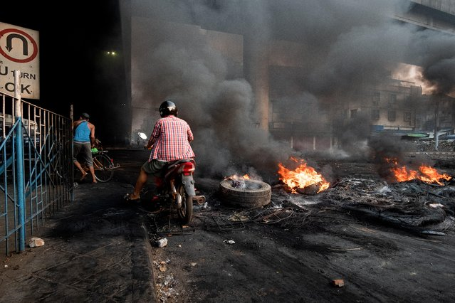 Smoke billows from burning tyres set alight to create smoke cover during a crackdown at Bayint Naung Junction in Yangon, Myanmar on March 16, 2021, in this photograph obtained by Reuters. (Photo by Reuters/Stringer)