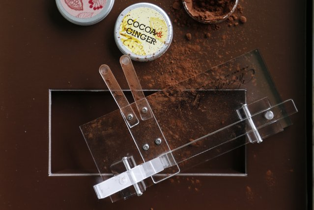 A Chocolate Shooter is displayed near cocoa powder in the factory of Belgian chocolatier Dominique Persoone in Bruges, February 3, 2015. (Photo by Francois Lenoir/Reuters)