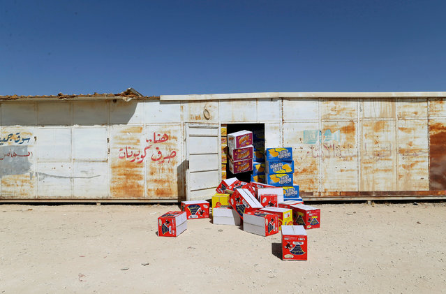 A Syrian refugee man (obscured) moves boxes of goods at his shop in Zaatari refugee camp near the border with Syria, in Mafraq, Jordan October 15, 2016. (Photo by Ammar Awad/Reuters)