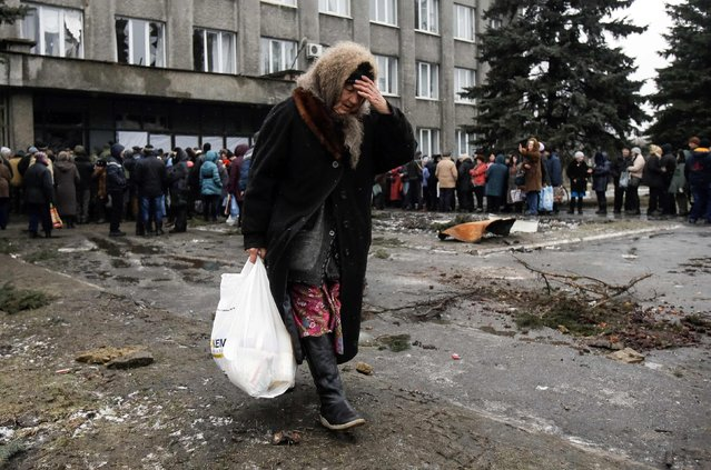 A woman carries a bag containing humanitarian aid in front of a delivery point in the Ukrainian forces-controlled town of Debaltseve, Donetsk region February 6, 2015. The rebels have been concentrating on Debaltseve, a rail hub where a government garrison has held out despite being nearly encircled. (Photo by Maxim Shemetov/Reuters)