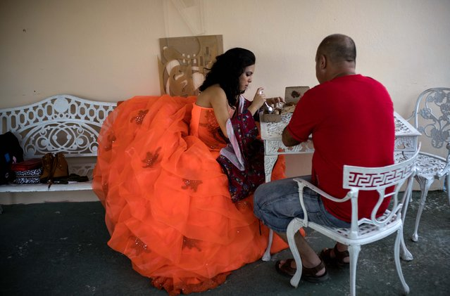 In this December 18, 2015 photo, Daniela Santos Torres, 14, breaks for a meal with her father Ivan Santos during a portrait session at EstudioMayer, which they hired to take her pictures and organize her birthday party in Havana, Cuba. (Photo by Ramon Espinosa/AP Photo)