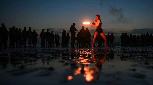 A fire juggler draws a crowd on Brighton beach on March 30, 2021 in Brighton, United Kingdom. (Photo by Mike Hewitt/Getty Images)