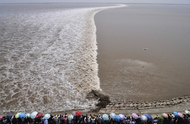 A remote controlled helicopter hovers over the Qiantang River as tourists gather on the river bank to see the soaring tide in Haining, Zhejiang province, on September 13, 2011. (Photo by Reuters/Stringer via The Atlantic)