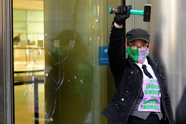 An activist from the Extinction Rebellion, a global environmental movement, takes part in a direct action at Barclays offices in Canary Wharf, London, Britain, April 7, 2021. (Photo by Toby Melville/Reuters)