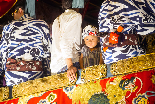 A Japanese child on top of a traditional wooden float during the Gion Festival in Kyoto, Japan, 15 July 2018. The annual Gion Festival is one of the most famous festivals in Japan. It starts every year on 15 July and continues through to the end of the month. During the festival the streets of Kyoto are lined with night stalls selling food, traditional Japanese sweets and games for children. The parade of giant traditional wooden floats, decorated with tapestries inspired by old European, Middle Eastern, Chinese and Japanese motifs, held on 17 July and 24 July are the highlight of the festival. The festival has been held annually since the year 970. (Photo by Everett Kennedy Brown/EPA/EFE)
