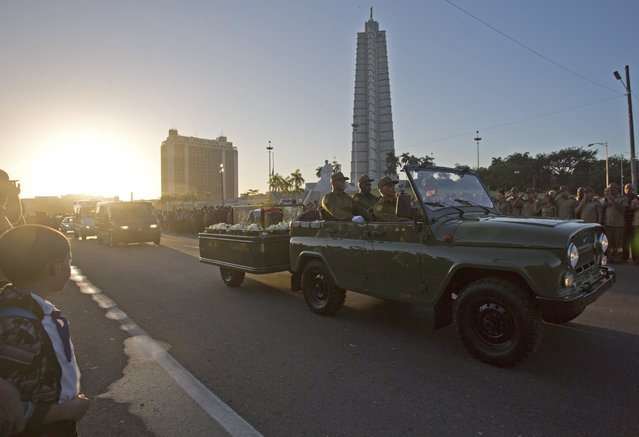 Placed in a small coffin covered by a Cuban flag the ashes of Cuban leader Fidel Castro are driven past the monument to Cuba's independence hero Jose Marti, through Revolution Plaza in Havana, Cuba, Wednesday November 30, 2016. (Photo by Desmond Boylan/AP Photo)