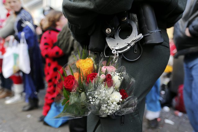 A police officer with flowers in her pocket stands guard during the traditional Rose Monday carnival parade in the western German city of Duesseldorf February 16, 2015. (Photo by Wolfgang Rattay/Reuters)