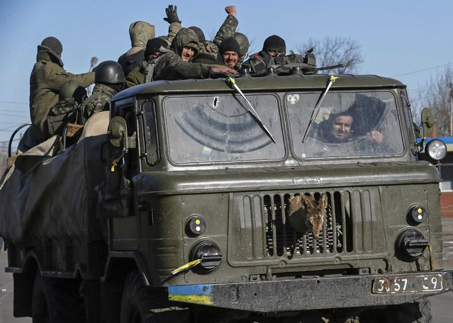 Ukrainian servicemen ride on a military vehicle as they leave area around Debaltseve, eastern Ukraine near Artemivsk, February 18, 2015. (Photo by Gleb Garanich/Reuters)