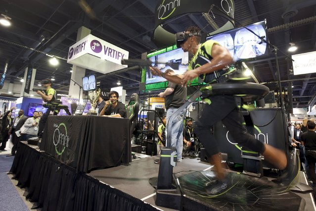 Jabril Muhummed (R) runs through a virtual world on a Virtuix Omni platform during the 2016 CES trade show in Las Vegas, Nevada January 8, 2016. The platform enables natural movement in 360 degrees during active virtual reality games. (Photo by Steve Marcus/Reuters)