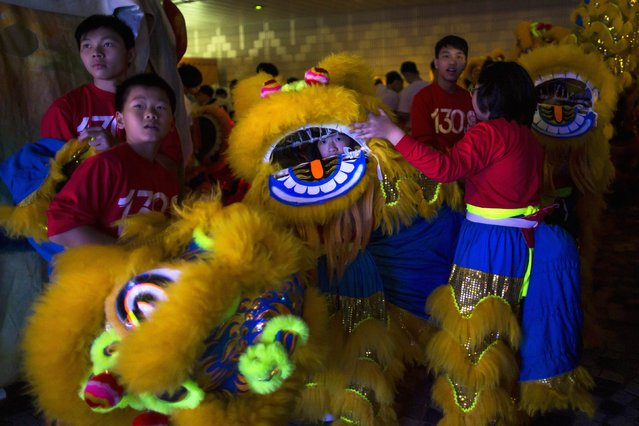Participants wait to perform a lion dance before a Chinese New Year evening parade at Hong Kong's Tsim Sha Tsui shopping district February 19, 2015. (Photo by Tyrone Siu/Reuters)