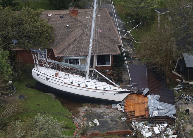 A sailboat is shoved up against a house and a collapsed garage Saturday, September 15, 2018, after heavy wind and rain from Florence, now a tropical storm, blew through New Bern, N.C. (Photo by Steve Helber/AP Photo)