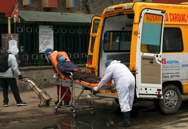 A patient suffering from coronavirus disease (COVID-19) is transferred from an ambulance towards the hospital as the major second coronavirus wave surges in Kathmandu, Nepal on May 4, 2021. (Photo by Navesh Chitrakar/Reuters)