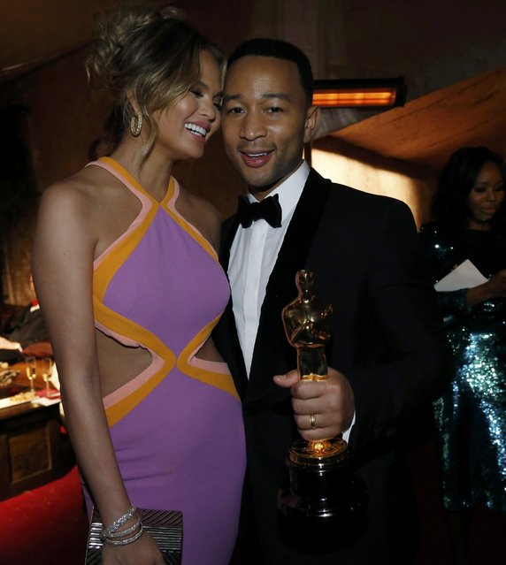 "Singer John Legend poses with his Oscar for best original song for ""Glory"" from the film ""Selma"" along with his wife model Chrissy Teigen at the Governor's Ball following the 87th Academy Awards in Hollywood, California February 22, 2015. (Photo by Mario Anzuoni/Reuters)"