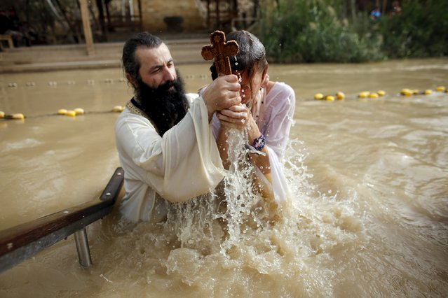 A Christian pilgrim is baptised as she takes part in a ceremony at the baptismal site known as Qasr el-Yahud on the banks of the Jordan River, near the West Bank city of Jericho January 18, 2016. (Photo by Nir Elias/Reuters)