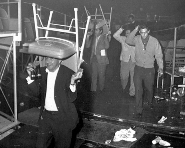 Fans use chairs to protect their heads as they flee from the Forum in Los Angeles, USA, December 7, 1968, after a riot broke out following the fight between Lionel Rose of Australia and Chucho Castillo of Mexico. Castillo's fans were angry over the result of a split decision in favor of Rose and created havoc in the arena. (Photo by AP Photo)