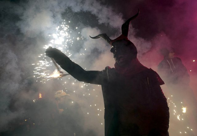 "A reveller dressed as a devil holds a stick with fireworks during traditional ""Correfocs"" (fire runs) to mark the end of the local festivities in Palma, on the Spain's Balearic Island of Mallorca, January 23, 2016. ""Correfocs"" are traditional celebrations in eastern Spain with people dressed as dancing devils while lighting fireworks among crowds of spectators. (Photo by Enrique Calvo/Reuters)"