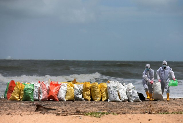Sri Lankan navy members remove debris washed off to a beach from the MV X-Press Pearl container ship which caught fire off the Colombo Harbour, on a beach in Ja-Ela, Sri Lanka May 27, 2021. (Photo by Dinuka Liyanawatte/Reuters)
